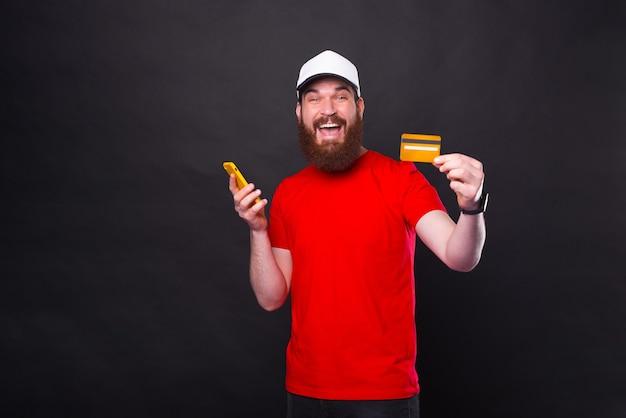 Foto van verbaasde jonge bebaarde man in rood t-shirt met creditcard