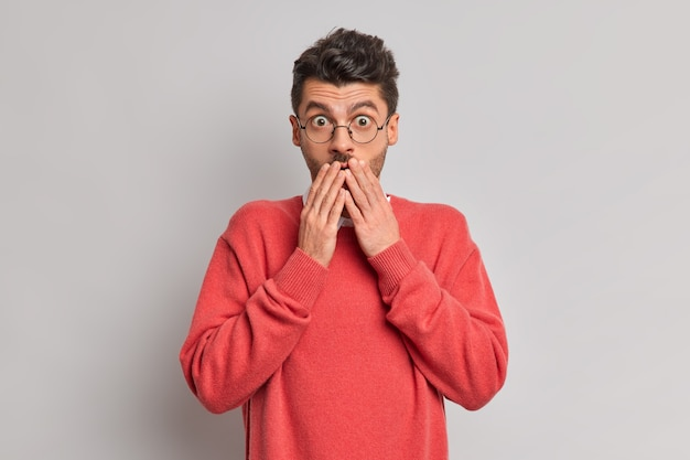 Foto van verbaasde jonge europese man houdt handen op de mond staart geschokt naar camera reageert op onverwachte relevantie