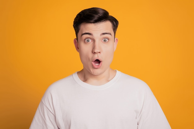 Foto van verbaasde jonge man met open mond geïsoleerd op gele achtergrond