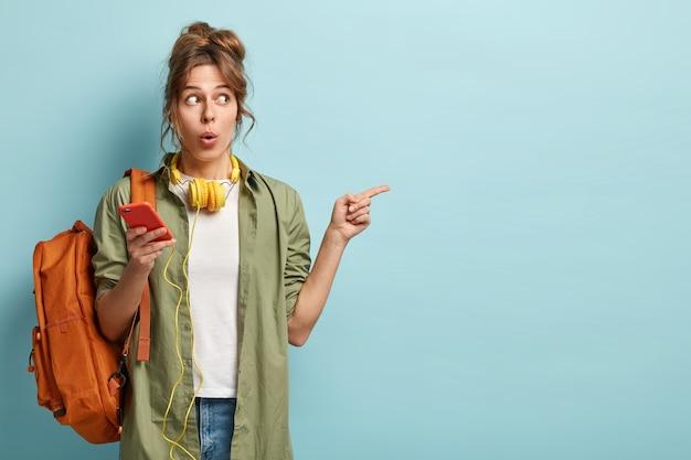 Foto van verbaasde jonge vrouw houdt mobiele, updates applicatie voor het luisteren naar favoriete liedje uit de afspeellijst