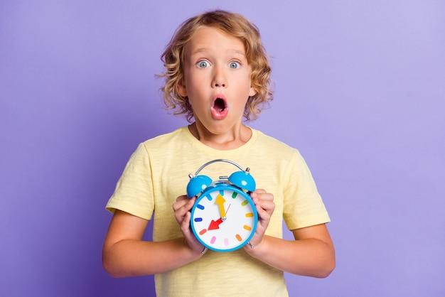 Foto van verbaasde kleine jongen voelt zich gefrustreerd houd klok gemist late tijd concept geïsoleerd over paarse kleur achtergrond