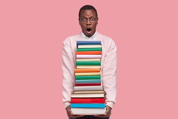 Foto van verbaasde knappe zwarte jongeman draagt veel boeken, houdt mond open, draagt vrijetijdskleding, verbaasd over moeilijke taken