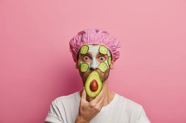 Foto van verbaasde man bedekt mond met de helft van avocado, draagt reinigende kleimasker met plakjes komkommer op gezicht, verfrist de huid, vermindert rimpels
