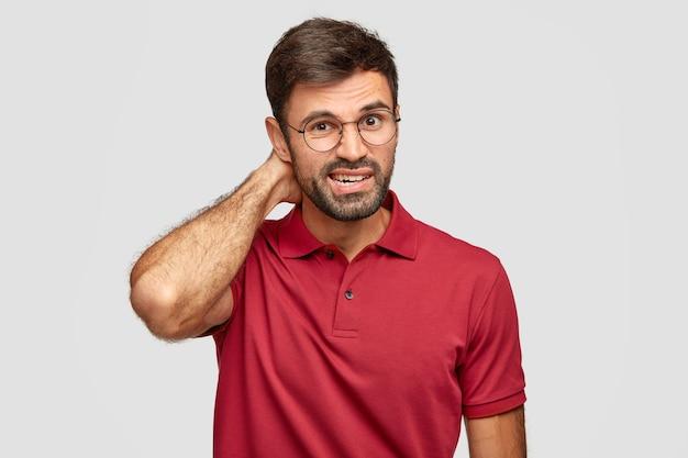 Foto van verbaasde man met stoppels, krassen hoofd