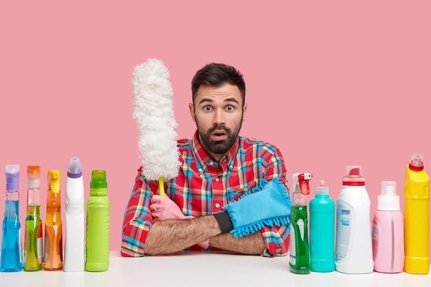 Foto van verbaasde ongeschoren europese mannelijke schoonmaakster draagt een geruit overhemd, houdt een witte borstel vast, omringd met flessen wasmiddel