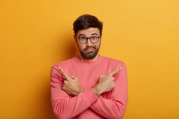 Foto van verbaasde ongeschoren man wijst zijwaarts, kruist armen over borst, twijfelt tussen twee keuzes of varianten, heeft een verbijsterde blik, draagt een bril en een roze trui, geïsoleerd op een gele muur.