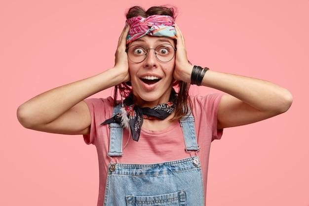 Foto van verbaasde, vrolijke hippiedame houdt beide handen op het hoofd, kan haar ogen niet geloven, staart met verbazing