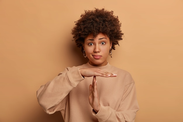 Foto van verbaasde vrouw met donkere huid maakt time-outgebaar, heeft ernstige gefrustreerde uitdrukking, krullend kapsel, gekleed in casual sweatshirt, poseert tegen beige muur, moet stoppen