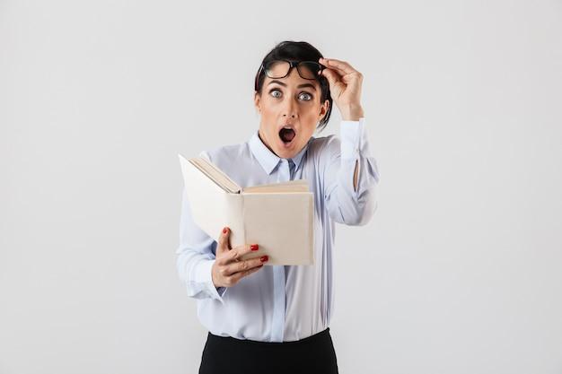Foto van verbaasde werkneemster die een bril draagt die een boek op kantoor leest, geïsoleerd over een witte muur