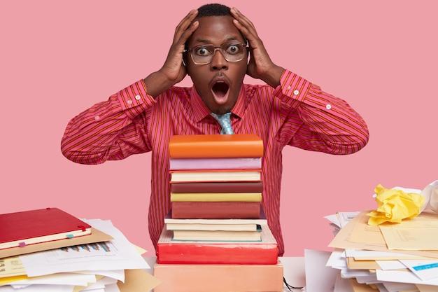 Foto van verbaasde zwarte man houdt de handen op het hoofd, staart met een overweldigde uitdrukking, moet alle boeken lezen voor het examen, stelt jaarverslag op