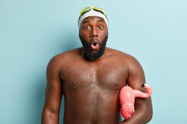 Foto van verbaasde zwarte man met natte huid, geschokt om veel mensen op het strand te zien, zwemt in zee met opgeblazen flamingo