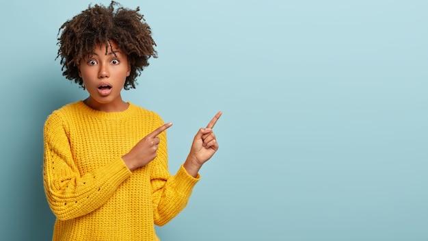 Foto van verbazend knappe vrouw schreeuwt van schokkend nieuws, wijst in de rechter lege hoek, draagt gele trui, verrast door onverwachte prijs, toont iets. kopieer ruimte voor aankondiging