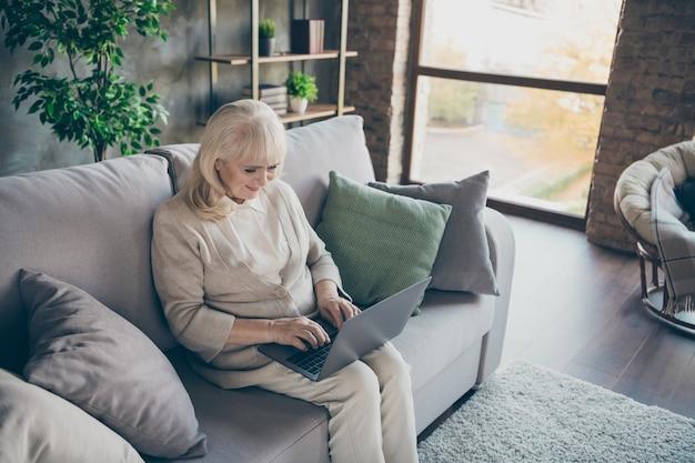 Foto van verbazingwekkende blonde leeftijd oma laptop lezen kleinkinderen e-mail typen antwoord zitcomfort sofa divan woonkamer binnenshuis