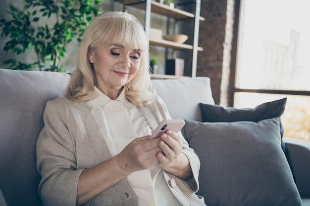 Foto van verbazingwekkende blonde schattige oude oma huiselijke goed humeur met behulp van telefoon lezen kleinkinderen e-mail moderne gebruiker zitten comfort sofa divan woonkamer binnenshuis