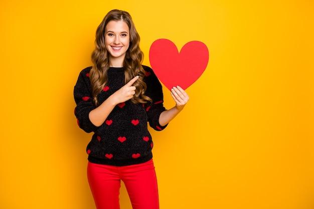 Foto van verbazingwekkende krullende dame amour houden groot papieren hart vinger creatief idee datum uitnodiging slijtage harten patroon trui rode broek
