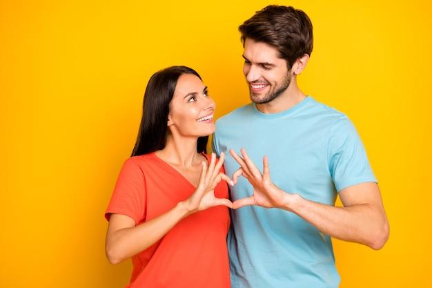 Foto van verbazingwekkende twee mensen man dame vieren valentijnsdag houden vingers hart figuur vorm kijken ogen dragen casual blauw oranje t-shirts geïsoleerde gele kleur muur
