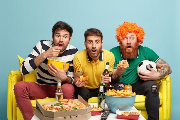 Foto van verbijsterde beste mannelijke vrienden staren naar het scherm van tv, houden bier vast, eten heerlijke pizza, geschokt door onverwacht resultaat van voetbalspel, zitten op comfortabele gele bank, verloren wedstrijd, geïsoleerd op blauw