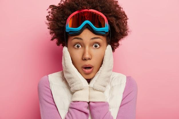 Foto van verbijsterde emotionele krullende vrouwelijke blikken met geschokte gezichtsuitdrukking naar de camera, houdt beide handen op de wangen, draagt een skibril voor snowboarden, geïsoleerd over roze studiomuur