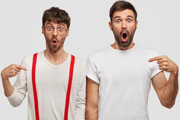 Foto van verbijsterde jonge blanke mannen metgezellen die naar elkaar wijzen, onverwacht nieuws horen, gekleed in witte kleren, tegen de muur staan. mensen, reactie en levensstijlconcept.