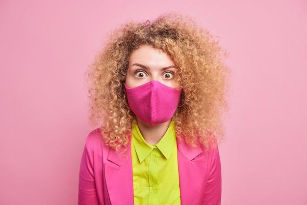 Foto van verdoofde vrouw in formele kleding bereidt zich voor op formele ontmoeting tijdens quarantaine draagt beschermend gezichtsmasker in één kleur met kleding geïsoleerd over roze muur. pandemisch concept