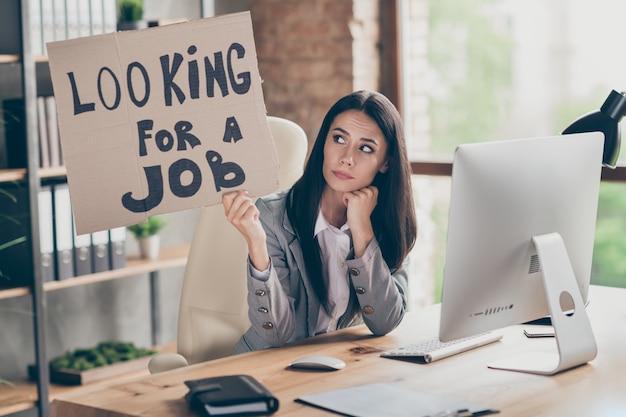 Foto van verdrietig, gefrustreerd, overstuur meisje voelt zich gestrest over haar bedrijf covid crisis verlies houd kartonnen tekst vast op zoek naar werkkleding blazerjasje in moderne werkstation