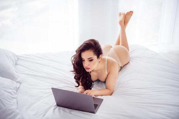 Foto van verleidelijke thuiswerker op afstand dame quarantaine online laptop chat klaar uitkleden op scherm fit lichaam voor geld schrijven lees vip klantbericht draag bikini liggend linnen slaapkamer binnenshuis