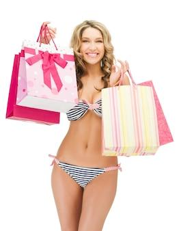Foto van verleidelijke vrouw in bikini met boodschappentassen
