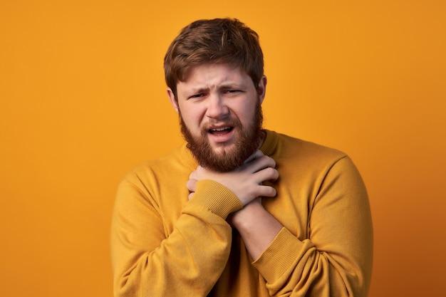Foto van vermoeide bebaarde man met negatieve gezichtsuitdrukking, lijdt aan verstikking, houdt de handen op de nek, kijkt ongenoegen naar de camera, heeft rood haar, casual gekleed, geïsoleerd op een witte muur