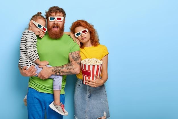 Foto van vermoeide dochter en moeder leunen naar echtgenoot die kijkt met een onder de indruk gelukkige uitdrukking, vrije tijd in de bioscoop doorbrengen, urenlang films kijken, een driedimensionale bril dragen, popcorn eten in een emmer