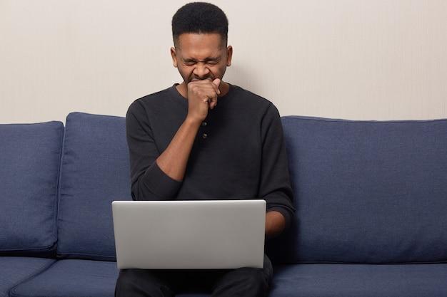Foto van vermoeide donkere huid voelt vermoeidheid van het werk op een laptopcomputer, gaapt en wil slapen, gekleed in zwarte trui