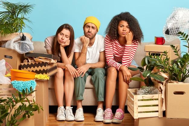 Foto van vermoeide drie verschillende studenten verhuizen naar een nieuwe flat, veranderen van woonplaats, hebben slaperige ontevreden uitdrukkingen, vermoeidheid na het uitpakken van bezittingen, omringd door items in kartonnen containers