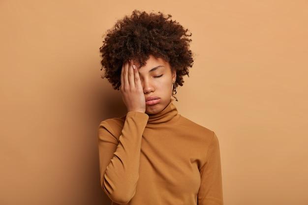 Foto van vermoeide krullende vrouw bedekt gezicht met palm, voelt zich overwerkt en vermoeidheid, wil slapen, kantelt hoofd, draagt casual coltrui