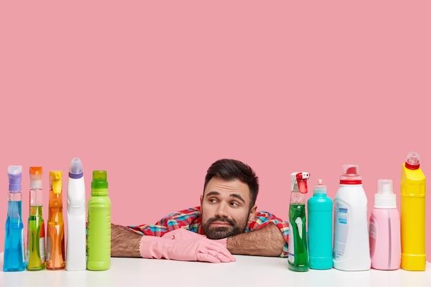 Foto van vermoeide ontevreden doordachte man leunt op tafel, geconcentreerd op flessen schoonmaakmiddel, draagt een geruit overhemd