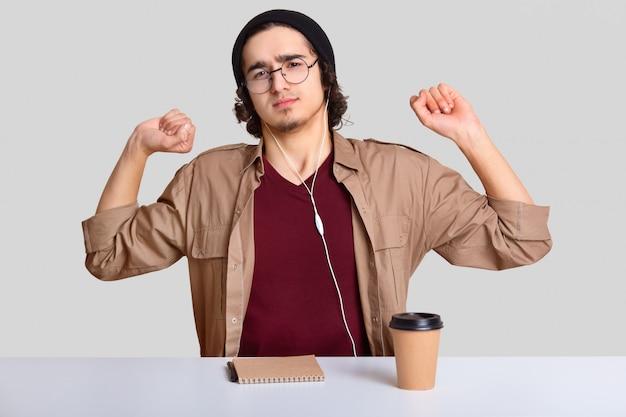 Foto van vermoeidheid man strekt zich uit terwijl zit op het bureaublad