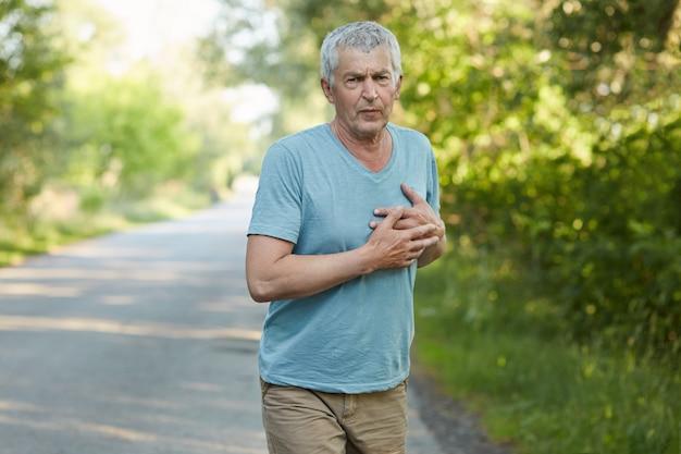 Foto van vermoeidheid volwassen man voelt pijn in het hart na het joggen