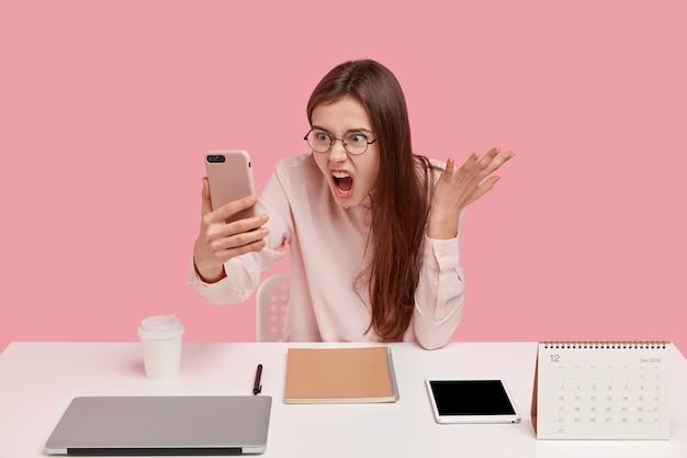 Foto van verontwaardigd geërgerd vrouw houdt moderne mobiele telefoon, maakt videogesprek, stelt met collega, poses op werkplek