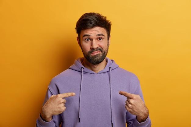 Foto van verontwaardigde bebaarde man wijst wijsvinger naar zichzelf, vraagt of je mij de schuld geeft, tuit zijn lippen en kijkt ontevreden, draagt casual paarse hoodie, poseert indoor tegen gele muur.
