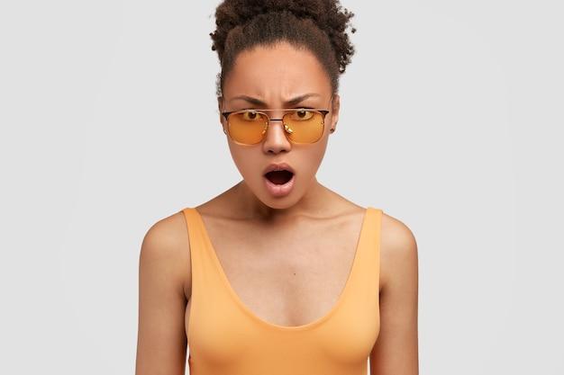 Foto van verontwaardigde donkere huid boze vrouw kijkt met ontevreden uitdrukking