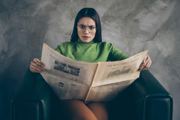 Foto van verontwaardigde geschokt vrouw in stomheid het lezen van nep verschrikkelijke krantenkoppen nieuws over haar bedrijf zittend in een fauteuil geïsoleerde grijze kleur muur betonnen achtergrond