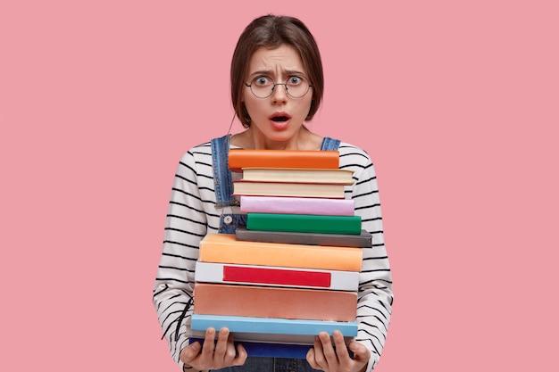 Foto van verontwaardigde jonge dame houdt mond open van negatieve emoties, draagt een ronde bril, houdt een zware stapel boeken vast