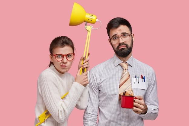 Foto van verontwaardigde mooie dame in bril met rode rand houdt gele lamp vast, portemonnees lippen, ontevreden ongeschoren man heeft geen zin om te werken