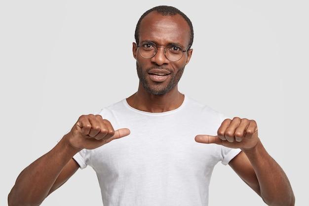 Foto van verontwaardigde ongeschoren african american mannelijke punten met beide duimen op zijn witte t-shirt