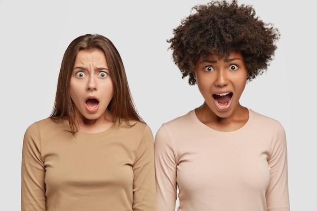 Foto van verontwaardigde ontevreden twee interraciale meisjes houden hun mond wijd open