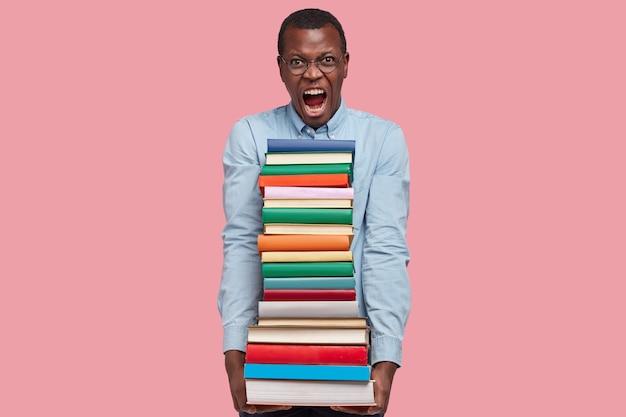 Foto van verontwaardigde zwarte man schreeuwt van ergernis, leest schoolboeken, geïrriteerd door veel taken, gekleed in formele kleding
