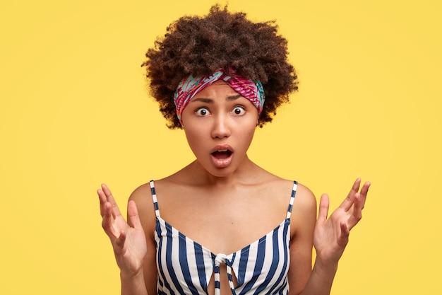 Foto van verontwaardigde zwarte vrouw houdt mond open, grijpt palmen, gekleed in vrijetijdskleding