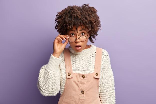 Foto van verrast afro-amerikaanse vrouw houdt hand op brilmontuur, staart direct geschokt, draagt witte trui met overall, drukt verwondering uit terwijl indrukwekkend nieuws wordt gehoord