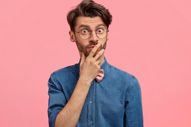 Foto van verrast bange blanke bebaarde man houdt hand op mond, kijkt met ogen vol geschoktheid, draagt stijlvol denim overhemd