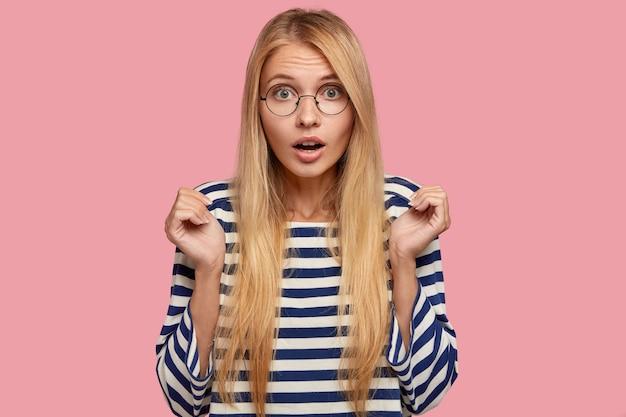 Foto van verrast blonde europese vrouw heeft lang haar, houdt de adem ingehouden, houdt handen met angst