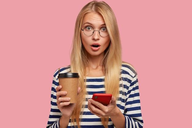 Foto van verrast blonde jonge vrouw met verrast gelaatsuitdrukking, maakt gebruik van mobiele telefoon