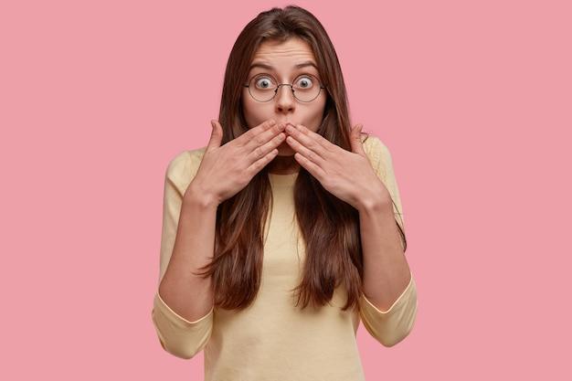 Foto van verrast donkerharige vrouw bedekt mond, kijkt met een angstige uitdrukking, reageert op iets verbazingwekkends